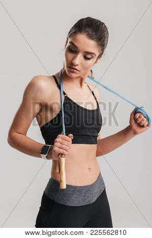 Portrait of gentle muscular woman looking aside and holding skipping rope on her neck isolated over gray background