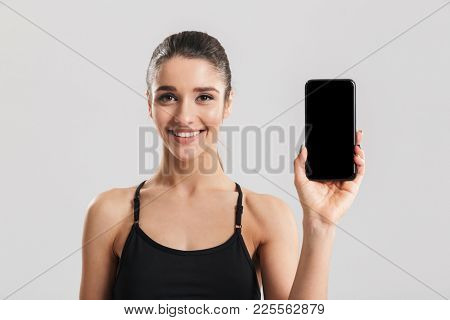 Portrait of well-built smiling woman showing black screen of smartphone on camera isolated over gray background