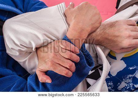 Kapap And Brazilian Jiu Jitsu Instructor In Traditional Kimono Demonstrates Ground Fighting Arm Lock