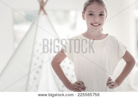 Being Inspired. Pretty Happy Vigorous Girl Smiling And Wearing A White- T-shirt And Holding Her Hand