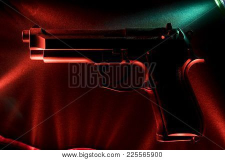 Pistol. Against The Background Of Green And Red Shades Of Material. Light Effect. Close-up.
