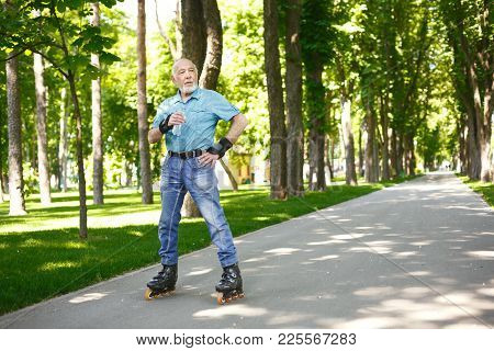 Elderly Man With Water Bottle. Senior Casual Man In Protective Wrist Gloves Having Break In Roller S