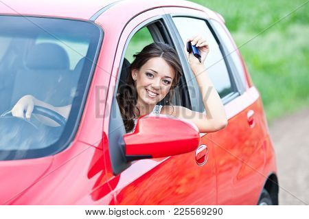 Happy Beautiful Woman In Red Car Holding Keys And Smiling