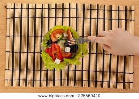 Picture Of Hand With Fork With Greek Salad On The Table