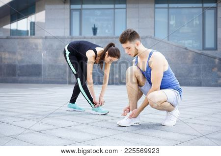 Concentrated Man And Woman Tying Shoelaces On Sneakers Before Running, Getting Ready For Jogging In