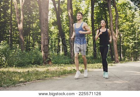 Young Happy Sporty Couple Jogging In Green Park During Morning Workout, Copy Space