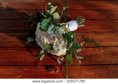 Wedding Bouquet Of Cream Roses Lies On A Wooden Surface. Wedding Rings.
