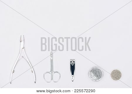 Top View Of Nail Nippers, Scissors And Different Glitter Isolated On White