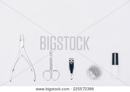 Top View Of Nail Nippers, Scissors And Glitter Isolated On White