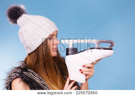Winter Sport Activity Concept. Girl Wearing Warm Hat And Furry Waistcoat Holding And Looking At Ice