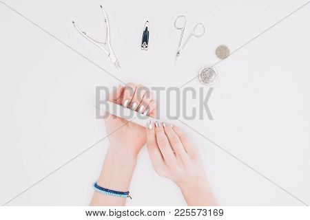 Cropped Image Of Woman Filing Nails With Nail File Isolated On White