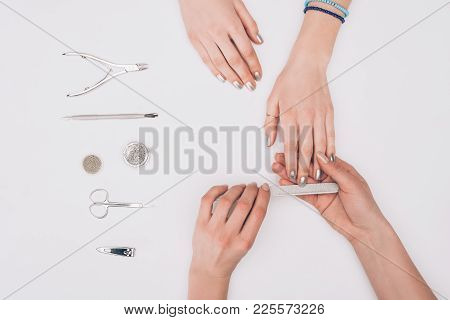 Cropped Image Of Manicurist Filing Nails To Customer With Nail File Isolated On White
