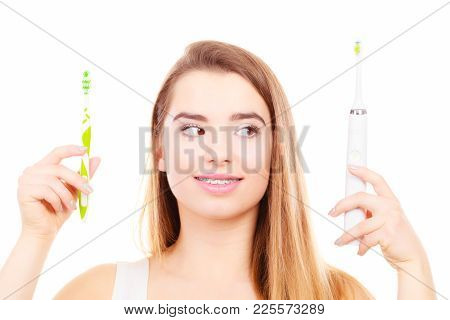 Woman With Braces Holding, Choosing Between Electric And Traditional Toothbrush, Have To Make Decisi