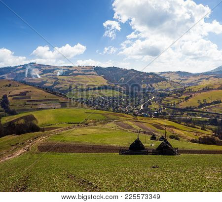 Rural Area In Carpathian Mountains. Haystacks On Grassy Agricultural Fields. Village Down In The Val