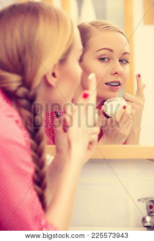Young Blonde Woman Applying Moisturizing Skin Cream On Face, Looking In Bathroom Mirror. Girl Taking
