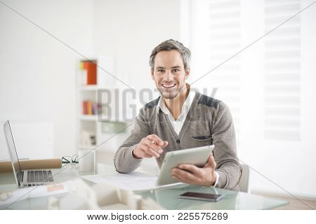 An Architect Working On The Office Holding A Tablet