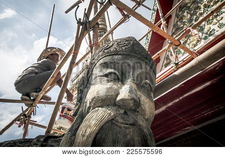 Bangkok, Thailand Noverber 29, 2017 : A Repairman Is Repairing A Roof In Wat Pho With A Giant Statue