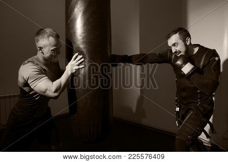 Strong Man In Boxing Gloves During Training.