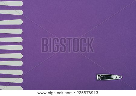 Top View Of Nail Nippers And Nail Files Isolated On Purple