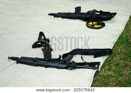 Airsoft Automatic Gun And Yellow Safety Glasses Lying On The Fabric And Grass. A Shooting Firing Ran