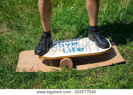 Men Feet On Deck For Balance Board On A Background Of Green Grass. Rocker-roller Boards Outdoor Trai