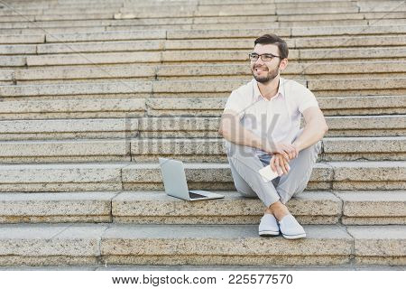 Pensive Businessman Having Rest Outdoors. Young Serene Salesman Sitting On Stairs With Laptop And Sm