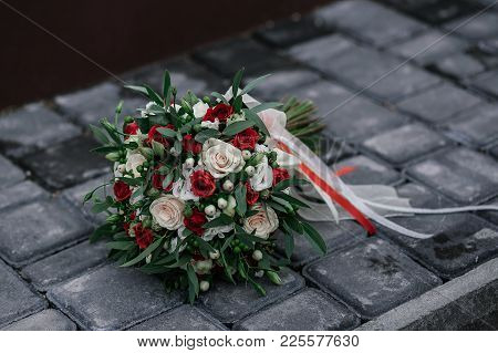 Wedding Bouquet Of Cream And Red Roses Lies On Stones Surface.