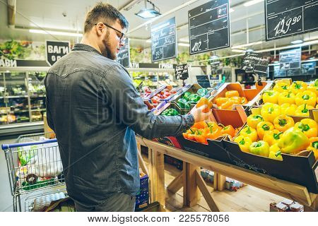 Man Seek Vegetables In Supermarket Stand Near Shelf With Salad Pepper