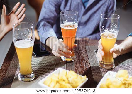 Friends Drinking Beer In Pub.friends Drinking Beer In Pub.