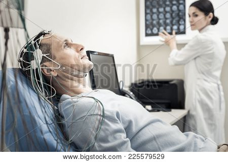Electro Scanning. Nice Pleasant Handsome Man Lying On The Medical Bed And Wearing Electronic Wires W