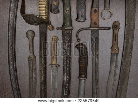 Armoury Display Of Historic Swords, Knives And Daggers In A Close Up Overhead Partial View On The Ha