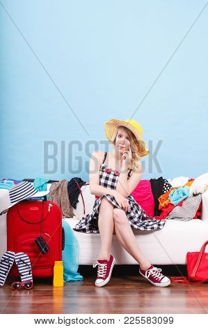 Packing Problems, Necessary Things During The Trip Concept. Woman Sitting On Sofa Holding Sun Hat, G