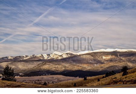 A Small Village Surrounded By Snow Capped Mountains Dotted With Green Evergreen Trees Under A Cloudy