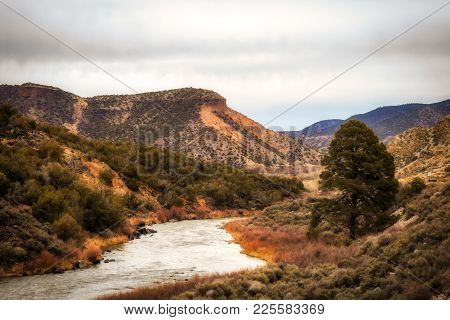 A Stream Winding Through Rocky Mountains Dotted With Shrubs In A Spring New Mexico Landscape