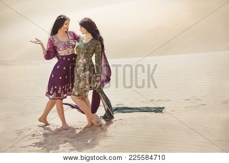 Travel Concept. Adventure Of Two Sisters Princesses Happy Standing In The Desert. Girlfriends Embrac