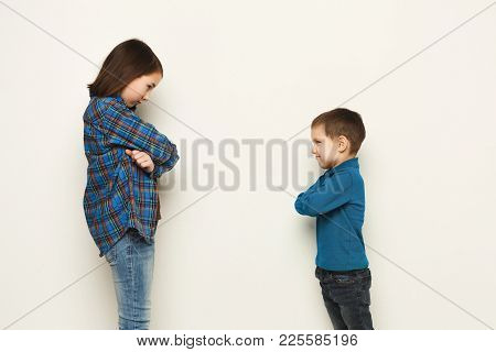Little Quarrel. Small Pretty Girl And Her Brother Standing Face To Face With Hands Crossed And Displ