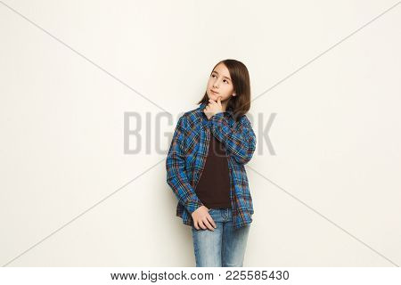 Portrait Of Pensive Little Girl With Mysterious Look. Thoughtful Kid Touch Her Chin And Dreaming, Wh