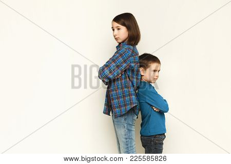 Little Quarrel. Small Pretty Girl And Her Brother Standing Back To Back With Hands Crossed And Displ