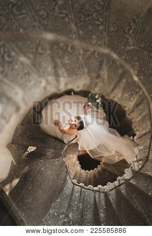 Beautiful Bride In Magnificent Dress Stands Alone On Stairs.