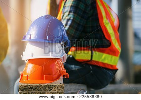 White, Orange And Blue Safety Helmet Stacked With Engineers Or Technician In Reflective Jacket In Co