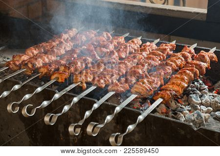 Cooking Of A Shashlik On A Grill On A Metal Skewer