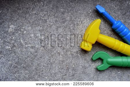 Toys Background. Kids Toys Top View. Toy Tools On Grey Grunge Background.  Three Kids Tools On Grey