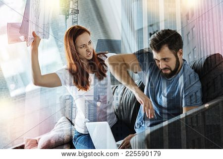 Go Away. Young Expressive Furious Woman Feeling Awful While Sitting On A Sofa And Trying Throw The D