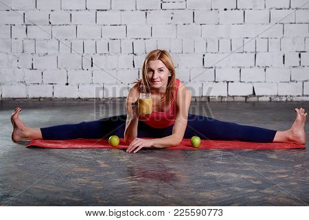 Woman Loves Pilates. Woman Is Resting After A Exercise. A Woman Resting After A Workout Sits On A Ru
