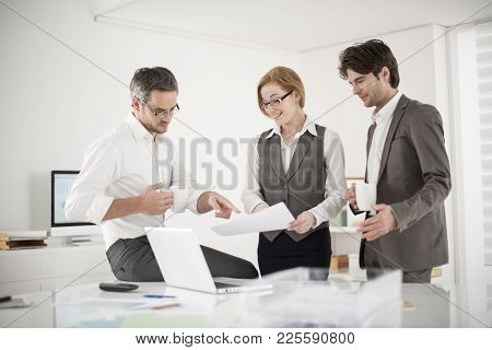 Three Colleagues Speaks About Business At Their Office
