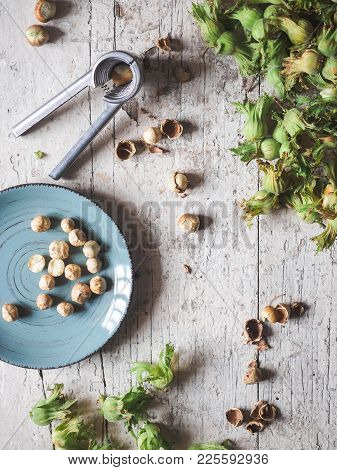 Top View Of Whole And Cracked Tasty Healthy Hazelnuts And Nut Crusher On Rustic Wooden Table