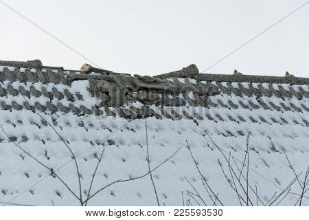 A Broken Tiled Roof Covered With Snow