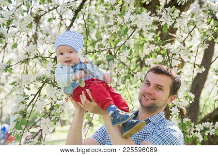 Young Happy Family Walking Outdoor. Parents Hold Child On Hands And Rejoice. They Are Happy Together