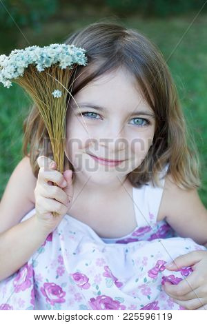 Smiling Little Girl Posing Outdoors With Flowers