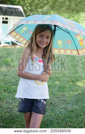 Smiling Little Girl Playing Outdoors With Colourful Umbrella